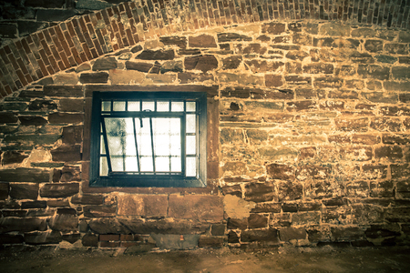 Rough stone interior wall with grunge window