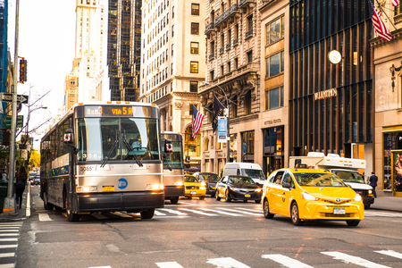 New York City, New York, USA - October 15, 2015:  Midtown Manhattan street view along the upscale shopping district on 5th Avenue with stores, buses and yellow taxicabs in view