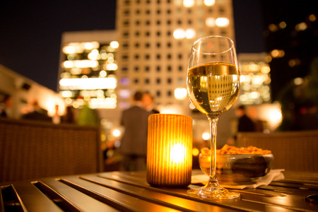Glass of white wine and candle with evening view of city buildings Reklamní fotografie