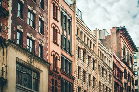 row of vintage new york city apartment buildings in a variety