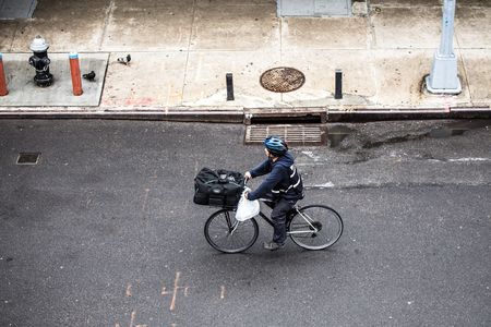 NEW YORK CITY - MARCH 29, 2018: New York City, Manhattan street scene viewed from above with man riding bicycle and pedestrians seen from Chelsea.