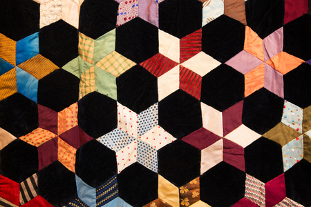 Geometric shapes and details on colorful fabric quilt blanket