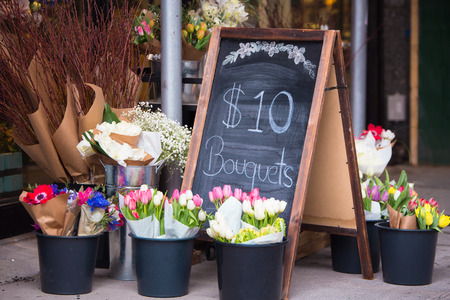 Charming florist sidewalk display of flowers and sign