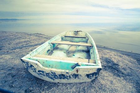 abandoned row boat along shore on Salton Sea in the California Desert Stock Photo