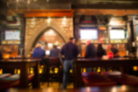 Defocused blur from Irish pub with unrecognizable people at the bar.