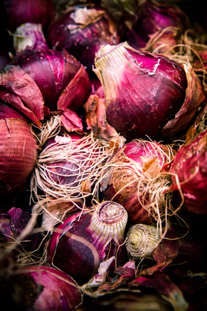 Crop of raw red Bermuda onions at farmers market Imagens