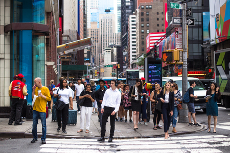 NEW YORK CITY - JULY 26, 2018:  Busy sidewalk in Times Square in Manhattan crowded with many people crossing street and billboards.