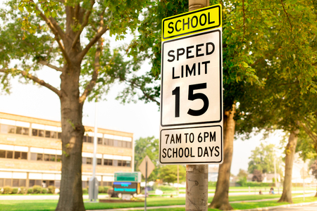 Sign indicating school zone speed limit of 15 miles per hour with school building seen in the background Stock Photo