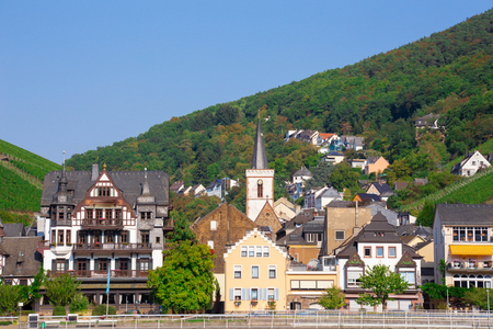 Charming village in Germany along the Rhine River with view of terraced vineyards,  hills and buildings
