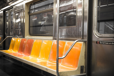 View inside New York City subway train car with vintage orange, red and yellow color seats 免版税图像