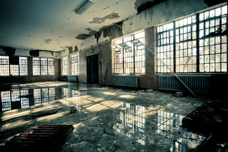 Interior of abandoned mental hospital with broken windows and water flood on floor