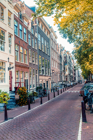 Street scene from Amsterdam with typical architecture of row of buildings alongside canal with non recognizable people in the background