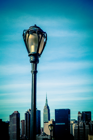 Black city lamp post with New York City Manhattan skyline in the background
