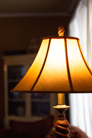 Illuminated lamp with shade in a dimly lit room Stock Photo