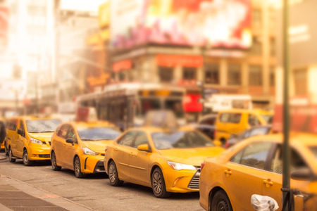 Defocused blur of a line of New York City yellow taxi cabs at rush hour in midtown Manhattan with sunlight Stock Photo - 118555659