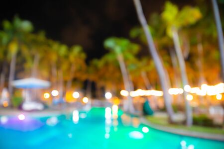 defocused blur of tropical resort hotel swimming pool at night with lights and palm trees Stock Photo