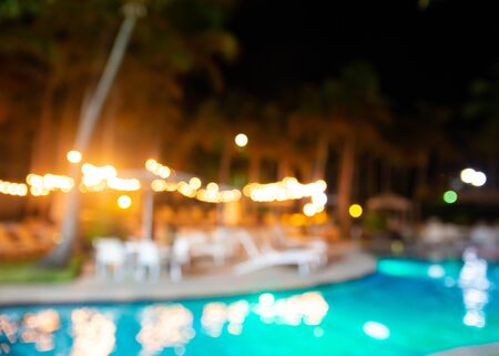 defocused blur of tropical resort hotel swimming pool at night with lights and palm trees Stockfoto