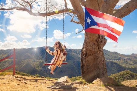 Feliz niña columpiándose de un árbol sobre el paisaje de montaña en la Curva del Arbol en Cayey Puerto Rico
