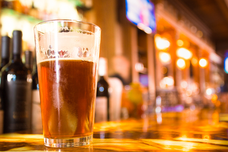 Glass Pint of amber beer with colorful blur of bar in background Stock Photo