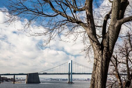 View of Throgs Neck Bridge and Long Island Sound seen from Bayside Queens toward the Bronx, New York City with bare tree in foreground Stockfoto