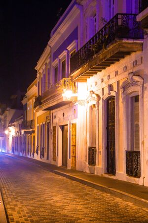 Empty street scene from Old San Juan Puerto Rico at night with buildings and cobblestones.