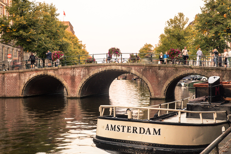 AMSTERDAM, NETHERLANDS - SEPTEMBER 1, 2018:  View of Amsterdam seen along the canal with bridge and boats in view.