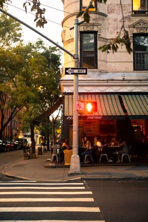 NEW YORK CITY - AUGUST 24, 2019: Outdoor restaurant street scene from the West Village in Manhattan with people dining on a Saturday evening.