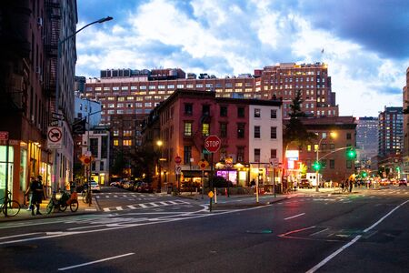 NEW YORK CITY - AUGUST 24, 2019: Street scene with stores, lights, people and cars, at night seen from Greenwich Village, West Village Manhattan.