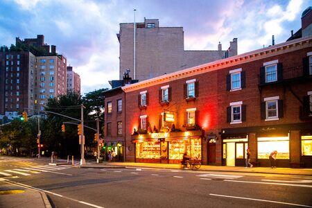 NEW YORK CITY - AUGUST 24, 2019: Street scene with stores lit at night seen from Greenwich Village, West Village Manhattan.