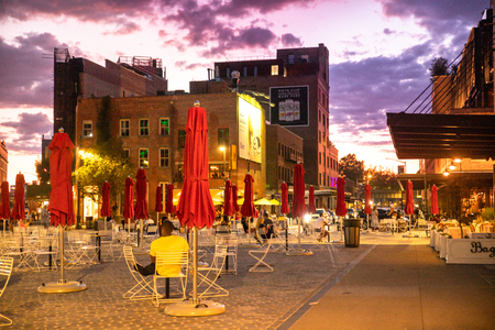 NEW YORK CITY - AUGUST 24, 2019: Sunset at the Gansevoort Plaza with people and outdoor tables