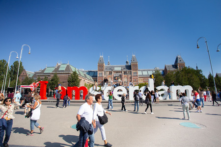 AMSTERDAM, NETHERLANDS - SEPTEMBER 2, 2018: View of visitors at the I Amsterdam sign with the historic Rijksmuseum in the background