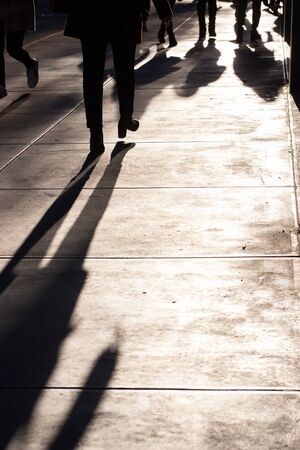 Unrecognizable people walking on New York City sidewalk with light and shadows. Copy space available.