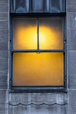 warmly lit window on urban building