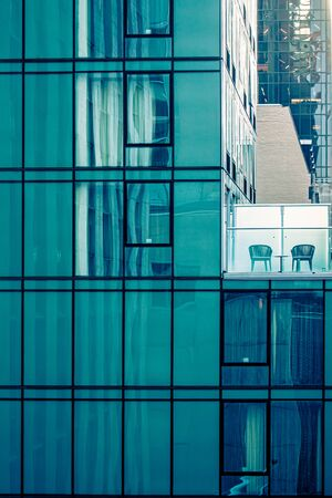 Urban exterior space with two chair on deck on glass building Stock fotó