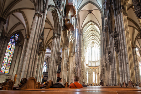 COLOGNE, GERMANY - SEPTEMBER 4, 2018: Interior view of historic Saint Peters Cathedral Domkirche with people and architecture Sajtókép
