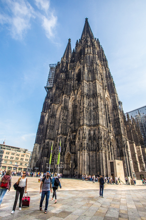 COLOGNE, GERMANY - SEPTEMBER 4, 2018: Exterior view of historic Saint Peters Cathedral Domkirche with people and architecture