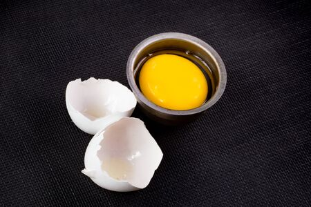 Egg on black with cracked shells and yolk Stock fotó