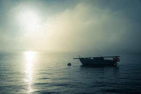 Single boat on water at sunset