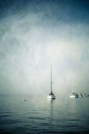 Vintage textured painterly image of sailboats in water on foggy day