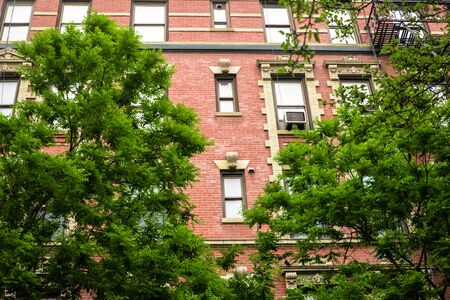 Typical New York City brick apartment building in spring surrounded by green trees. 免版税图像