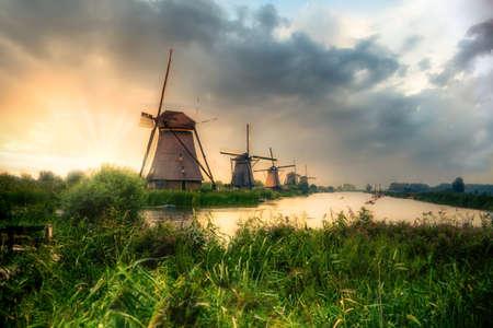 Beautiful Dutch windmills and landscape under dramatic sunset sky 免版税图像