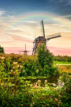 Beautiful Dutch windmills and landscape under dramatic sunset sky and rainbow 免版税图像