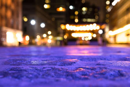 Blurred backdrop image of cobblestone street and lights from New York City.