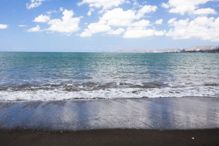 Beautiful black sand beach and ocean at shoreline seen from Puerto Rico