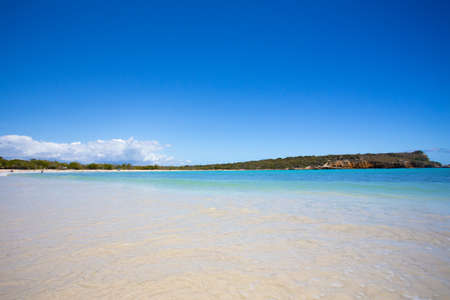 Idyllic beach scene with clear blue water, blue sky and sandy shore seen from Puerto Rico
