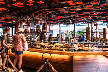 New York City, New York, USA - July 15, 2021: View inside of the Starbucks Reserve New York Roastery with people visible seen from Chelsea.