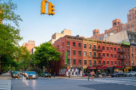 New York City, New York, USA - July 15, 2021:  Street scene from Chelsea neighborhood in Manhattan of intersection with people, buildings and cars.