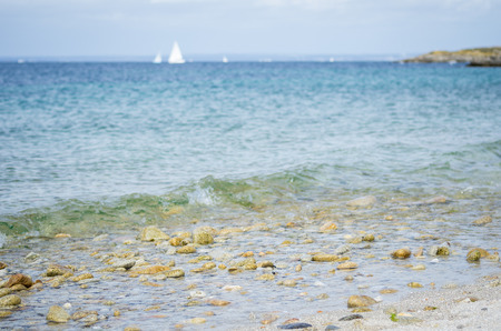 Pebble beach, with blue sea and white boat in the background. Photographed in Glenan Isles (France) Stockfoto