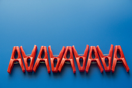 red clothes peg on blue background Stock Photo