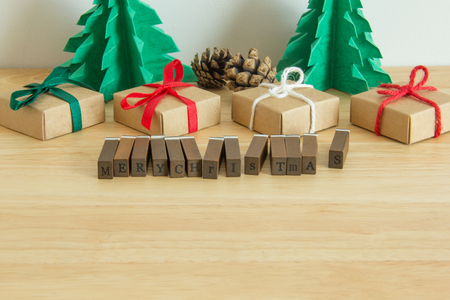 Paper christmas tree with presents, pines and the word Merry Christmas written in wooden letterpress